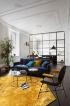 an-elegant-living-room-with-a-navy-sofa-a-black-and-yellow-chair-a-yellow-rug-and-pillows-plus-potted-plants