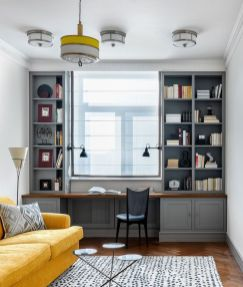 an-elegant-vintage-home-office-with-a-built-in-grey-storage-unit-a-vintage-chair-a-yellow-sofa-a-coffee-table-trio-and-a-pendant-lamp