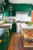 an-emerald-kitchen-with-a-white-subway-tile-backsplash-elegant-gold-touches-and-a-bright-boho-rug