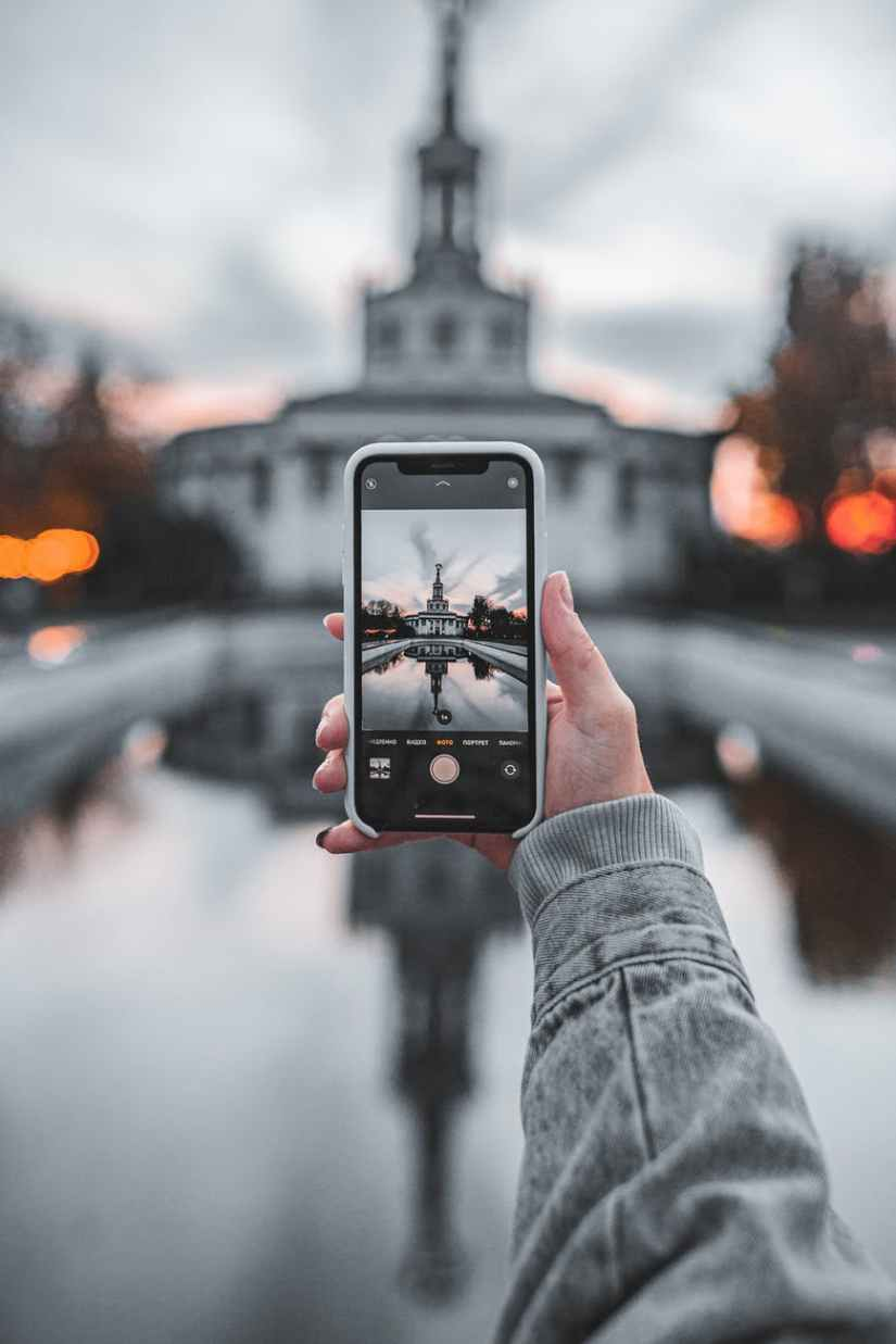 crop unrecognizable woman taking photo of aged building on smartphone during vacation
