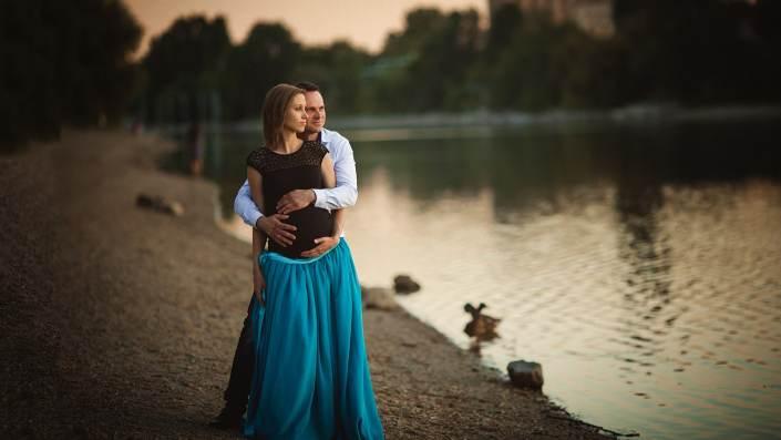 folyó parton öleli a férje a kismamát