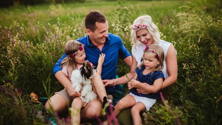 család ül egy réten