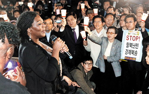 Boney M lead singer Liz Mitchell sings during a candle-lit rally held to demand China stop repatriating North Korean refugees, near the Chinese Embassy in Seoul on Thursday.