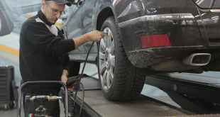 serious car mechanic pumping up car wheel in modern service garage