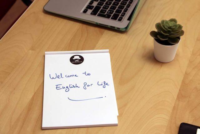 """Un notepad posé sur le bureau de Robert Haggart avec écrit dessus """" Welcome to English For Life"""""""