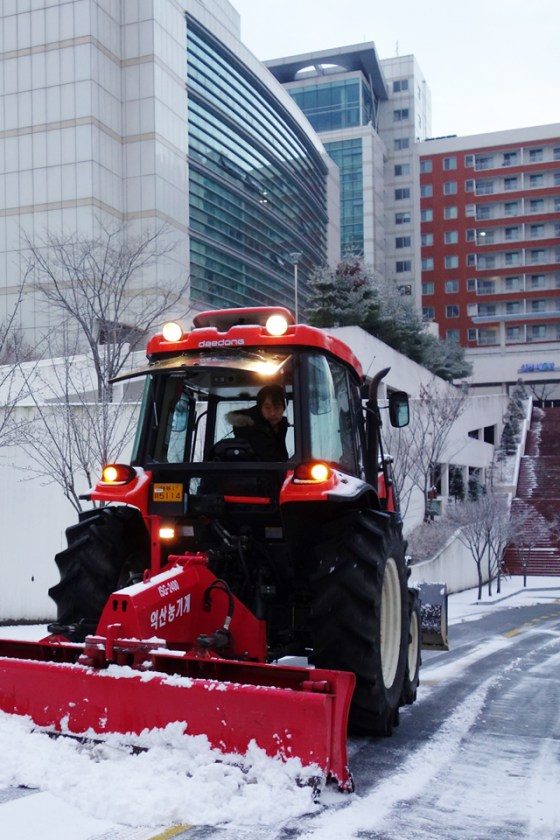 With about an hour till classes begin at Kangnam University, a snowplow operator busily finishes clearing last night's snow on campus. (Photo: Charles Ian Chun)