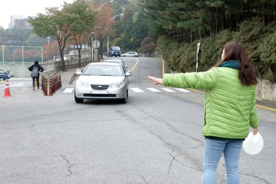As Kangnam University prepares for its 2013 Fall Festival, 1st-year business administration student Kim Abin works a two-hour shift directing on-campus traffic. (Photo: Charles Ian Chun)