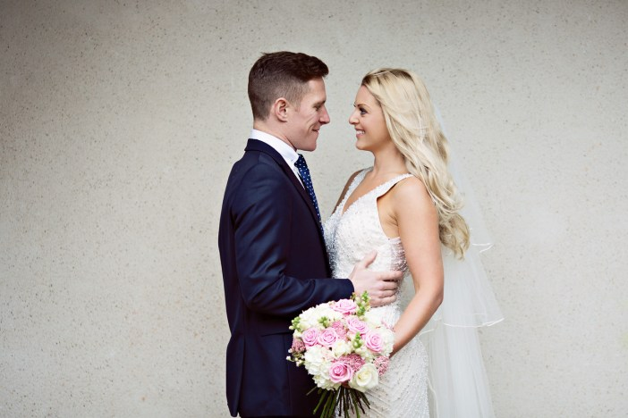Bride and Groom with a colourful bouquet at Lancaster House