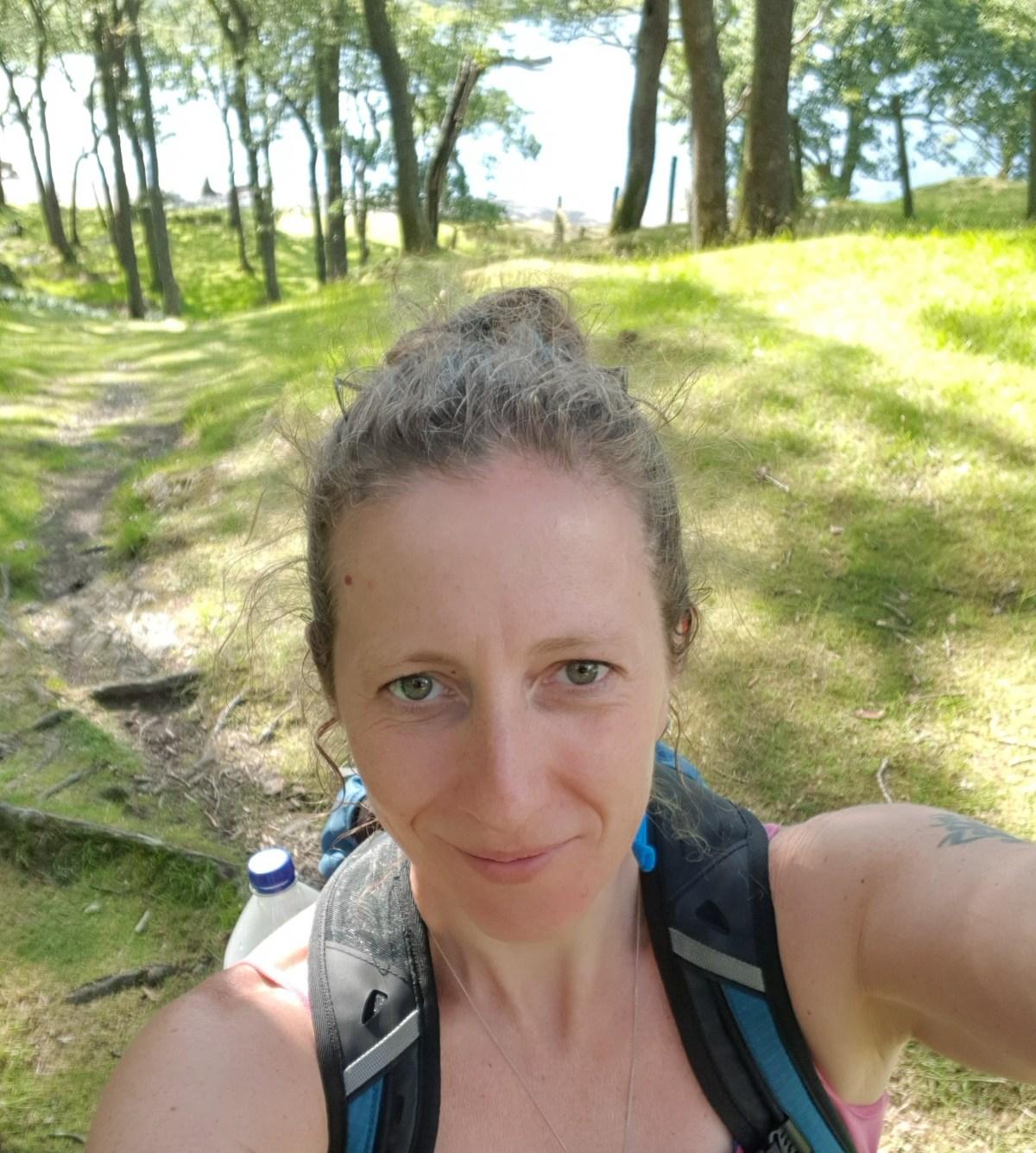 Rachel walking in the woods by a lake
