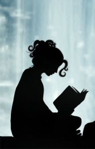 A girl in shadow reading a book