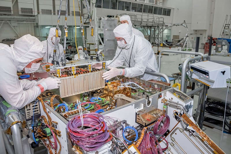 Technicians working on the Mars 2020 rover at NASA's Jet Propulsion Laboratory install the rover motor controller assembly, the electrical heart of the rover's mobility and motion systems.