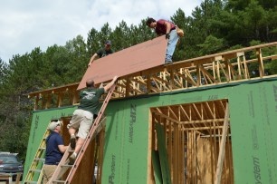 Ted, Mike, Ben, and I lift sheathing to the roof.