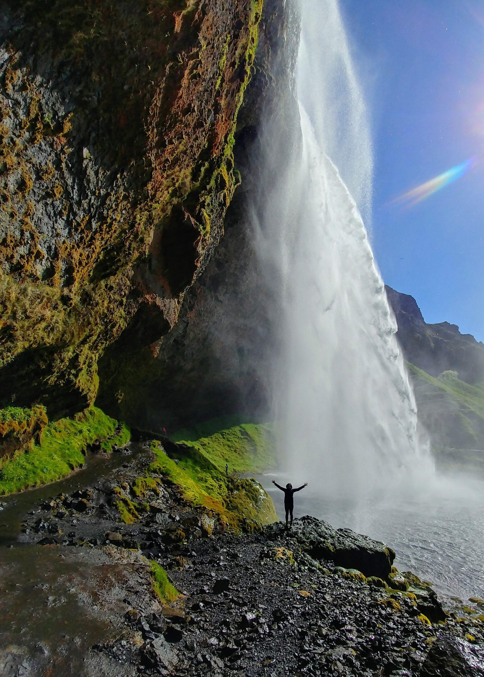 person standing under waterfall.jpg