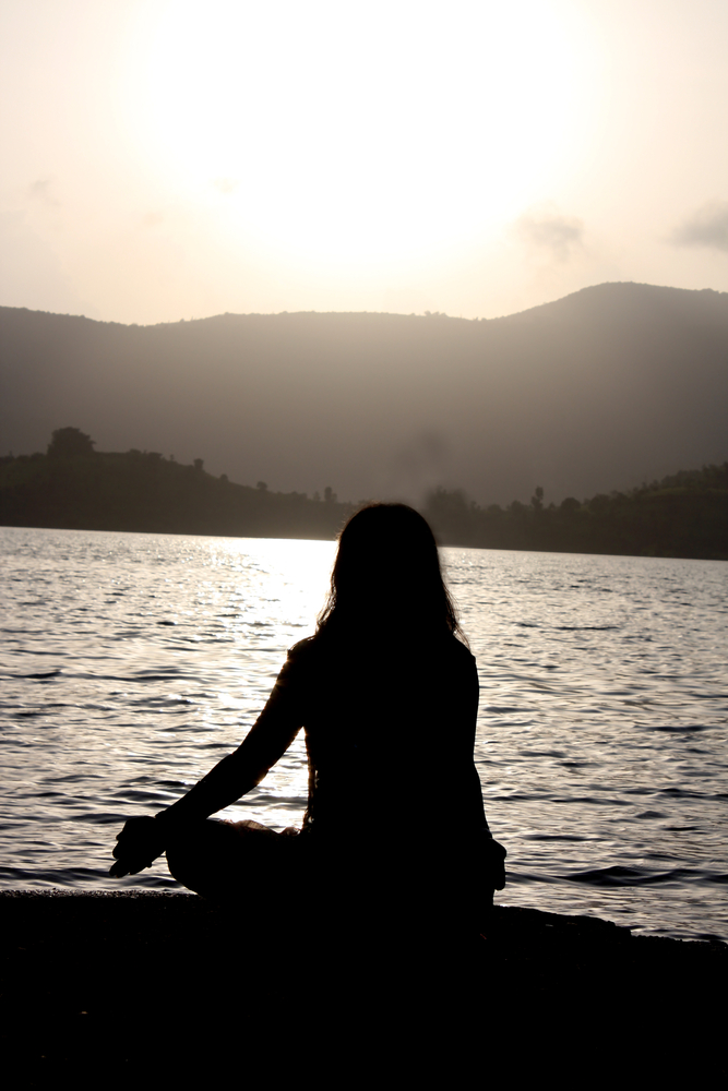 A woman meditating on the riverbanks, in the morning.