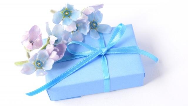 水色の包装紙に包まれたプレゼントと花びら