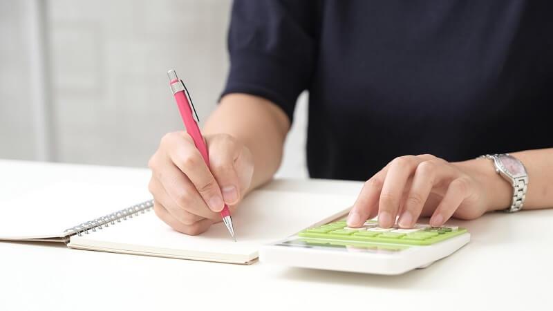 計算しながらノートに書き込む女性