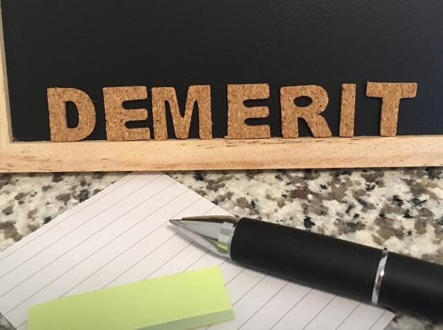 黒板に「DEMERIT」の文字
