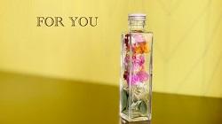 ガラス瓶に入った花びらと「FOR YOU」の文字