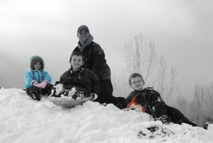 family playing on snow bank
