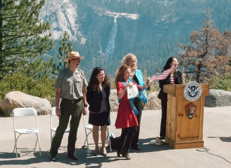 A newly naturalized citizen shows off her certificate of Naturalization in Yosemite National Park. Credit: NPS