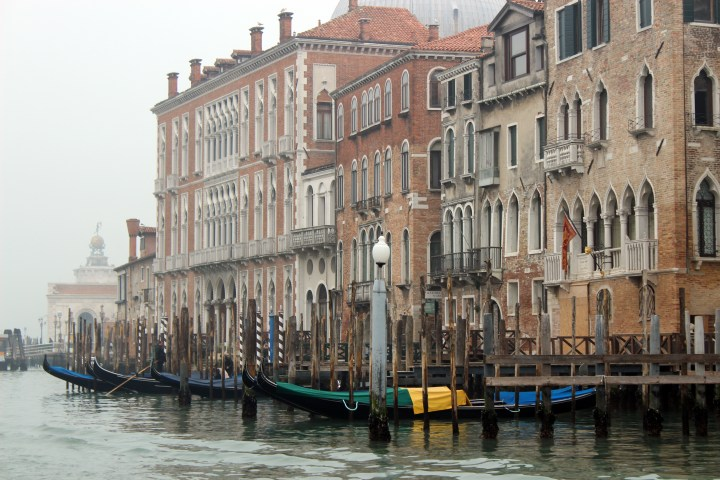 Gondolas in a row on the Grand Canal in Venice Italy