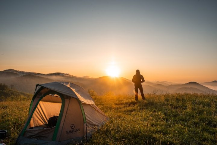 Camper watching sunrise over mountains