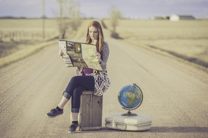 ways to travel without flying: girl with long red hair sits in road with her luggage reading a map