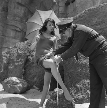 Policeman Chuck Peyton checks to see if actress Myrna Ross's bathing suit complies with 1933 Redondo Beach ordinance banning women's suits that are more than 3 in. above knee,1964.