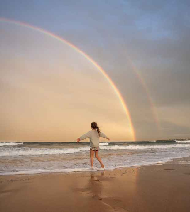 anonymous woman on beach with rainbow