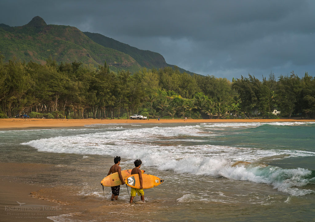 Photo: Pair of young male Surfers enter the surf water at Anahola Beach Park, Kauai, Hawaii