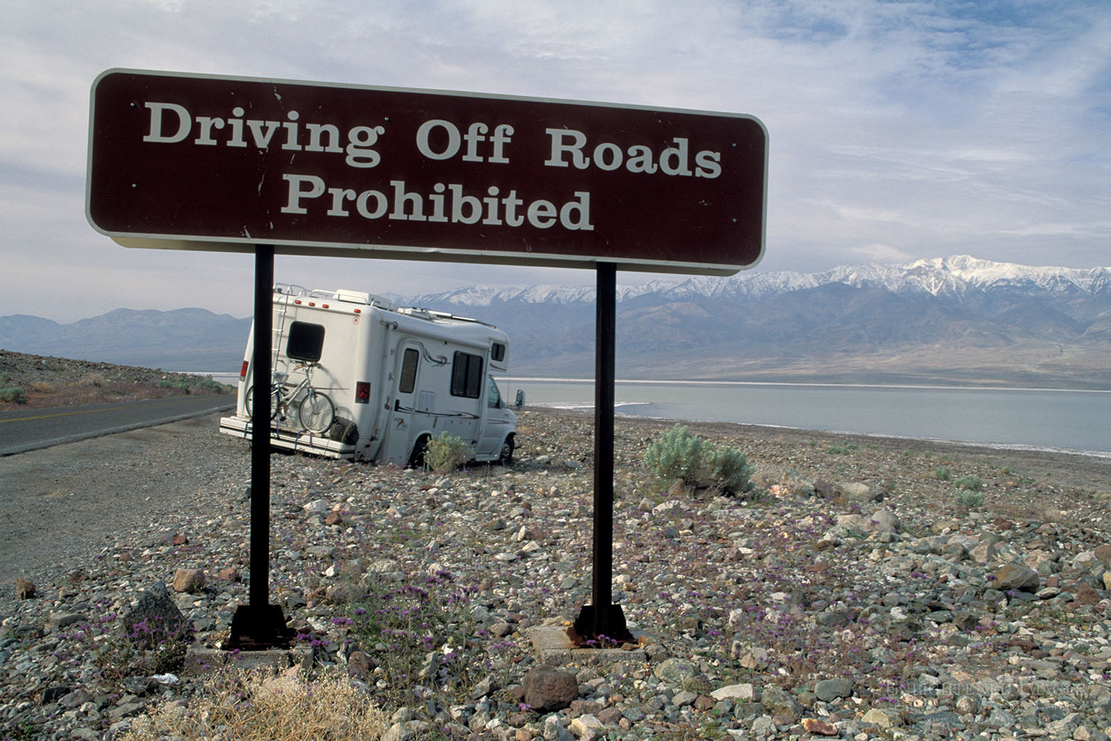 Photo: Driving off-road prohibited; Tourist RV tavel Camper stuck in desert rocks after driving offroad next to warning sign, near Badwater, Death Valley National Park, California