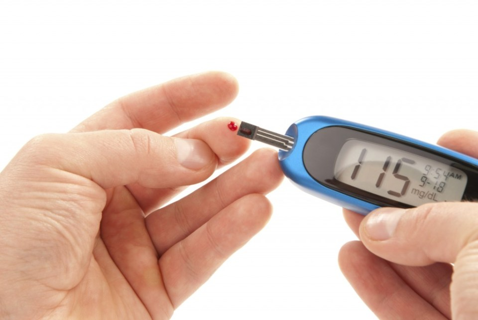 Diabetic patient doing glucose level blood test using ultra mini glucometer and small drop of blood from finger and test strips isolated on a white background. Device shows 115  mg/dL which is normal
