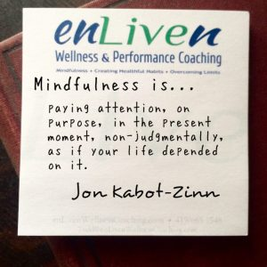 """Jon Kabot-Zinn quote on an Enliven Wellness Coaching sticky note, """"Mindfulness is paying attention, on purpose, in the present moment, non-judgmentally, as if your life depended on it."""""""