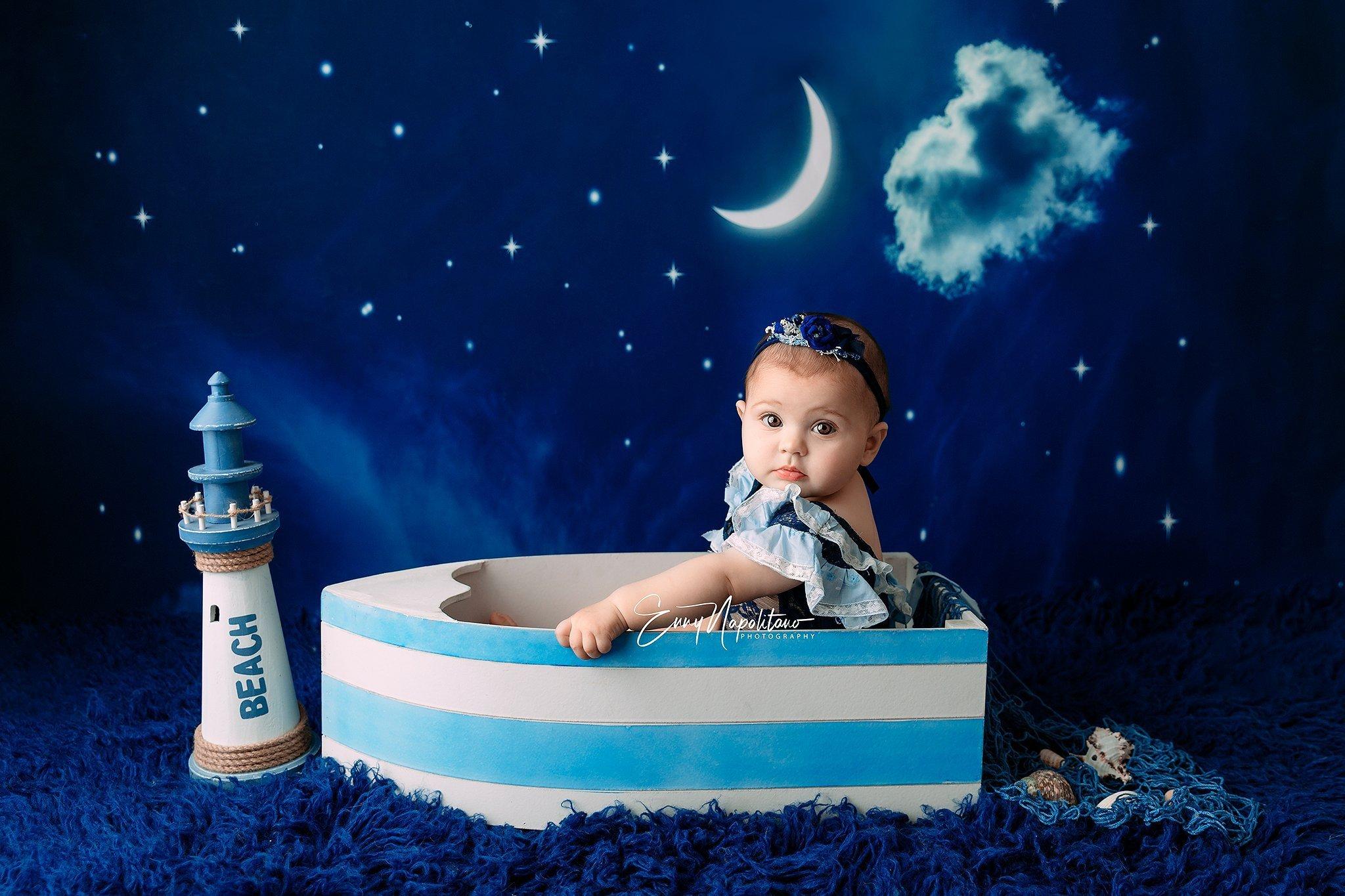 Fotografia di una bambina di 7 mesi in una barchetta sotto le stelle e la luna