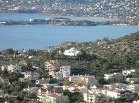 Ο ιερός ναός Κοιμήσεως τής Θεοτόκου και στο βάθος το Λαγονήσι με το ξενοδοχείο Grand Resort