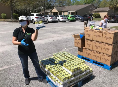 Vicky Ingalls, EP board member and volunteer with the Community Buddy System, stands near a pallet of pickles at a distribution at Brighton Place.