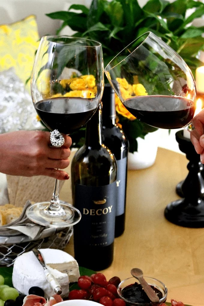 hands toasting with red wine served in wine glasses, and cheese platter in the bottom