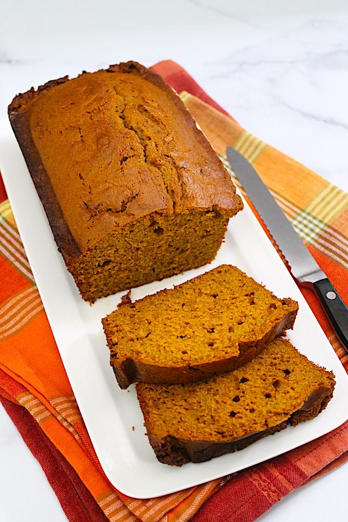 Sliced pumpkin spice bread with orange zest.
