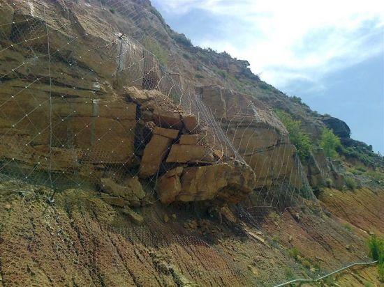 una red de cable sujetando 24 toneladas de piedras... lo normal