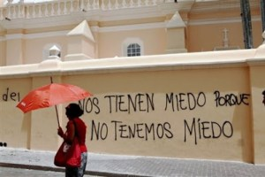 """A woman walks past a graffiti written by supporters of Honduras' ousted president Manuel Zelaya on one of the outer walls of Tegucigalpa's cathedral, that reads in Spanish: """"They fear us because we don't have fear"""" in Tegucigalpa, Sunday, July 12, 2009. Honduran authorities on Sunday lifted a curfew imposed since the ousting of President Manuel Zelaya two weeks ago _ a sign the interim government is trying to restore normality to life in the crisis-gripped country. (AP Photo/Rodrigo Abd)"""