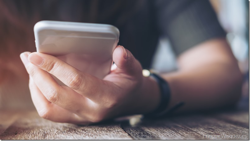 Closeup image of a woman's hand holding and using at smart phone on wooden table in vintage cafe