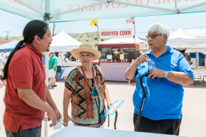 Advocate Sonny Weahkee, part Navajo and and part Pueblo,  promotes health insurance for Native Americans through the New Mexico health exchange during the annual feast day at the Santo Domingo Pueblo on Tuesday, August 4, 2015 (Photo by Heidi de Marco/Kaiser Health News).