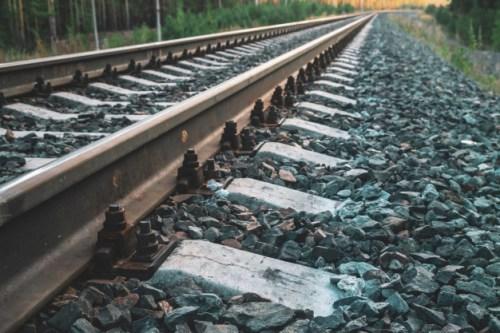 tornillos-cerca-ferrocarril-viaje-viaje-via-tren-luz-sol-patron-tonos-azul-oscuro_102332-2998