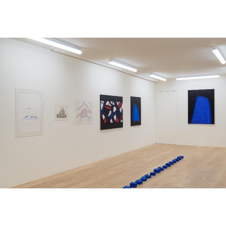 """Vue de l'exposition """"Le Phénomène Verame"""", avec de gauche à droite  : «Sans titre», dessin, 1983, «For Peace Junction Sinai», dessin, circa 1980, «Sans titre», dessin, circa 1980, «Sans titre», acrylique sur toile, 1987, «Sans titre», acrylique sur toile, circa 1980-90, «Sans titre», acrylique sur toile, 1987, «49 pavés de Paris» (d'une série de 50), pavé bleu, 2019. Photographie : © Grégory Copitet - Enseigne des Oudin"""