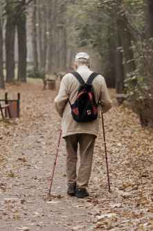 Older gentleman walking down path with walking sticks