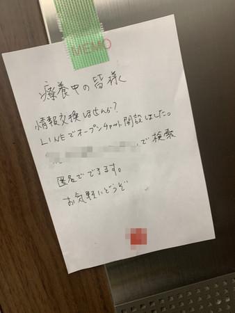 療養ホテル内のエレベーターホールに貼られたチャットの案内。ホテル室内 のメモに書かれている。