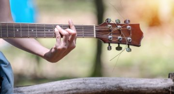 Hands of young woman holding acoustic guitar