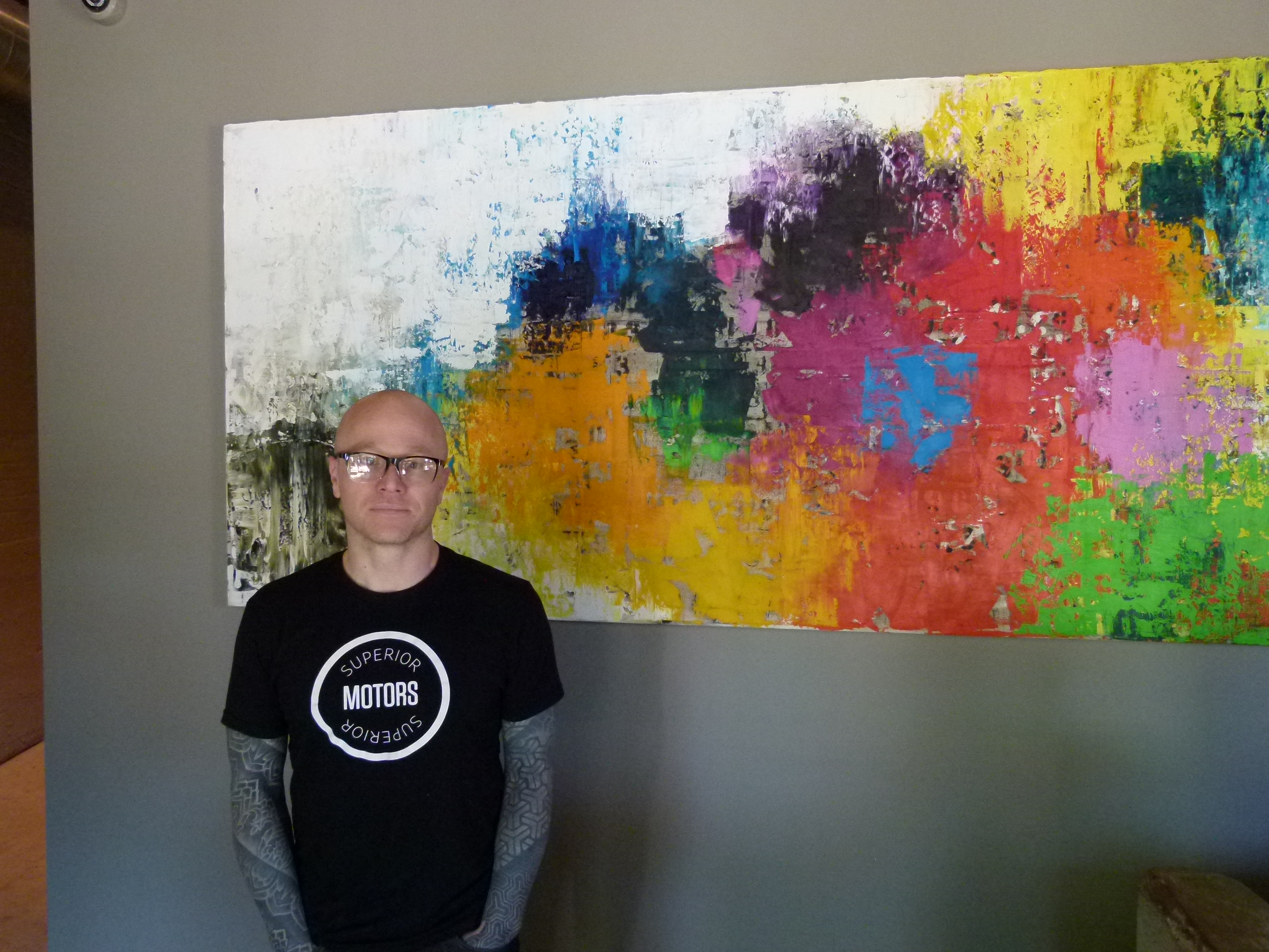 Chef/owner Kevin Sousa at the host station of Superior Motors in front of a painting by Pittsburgh artist Mia Tarducci.
