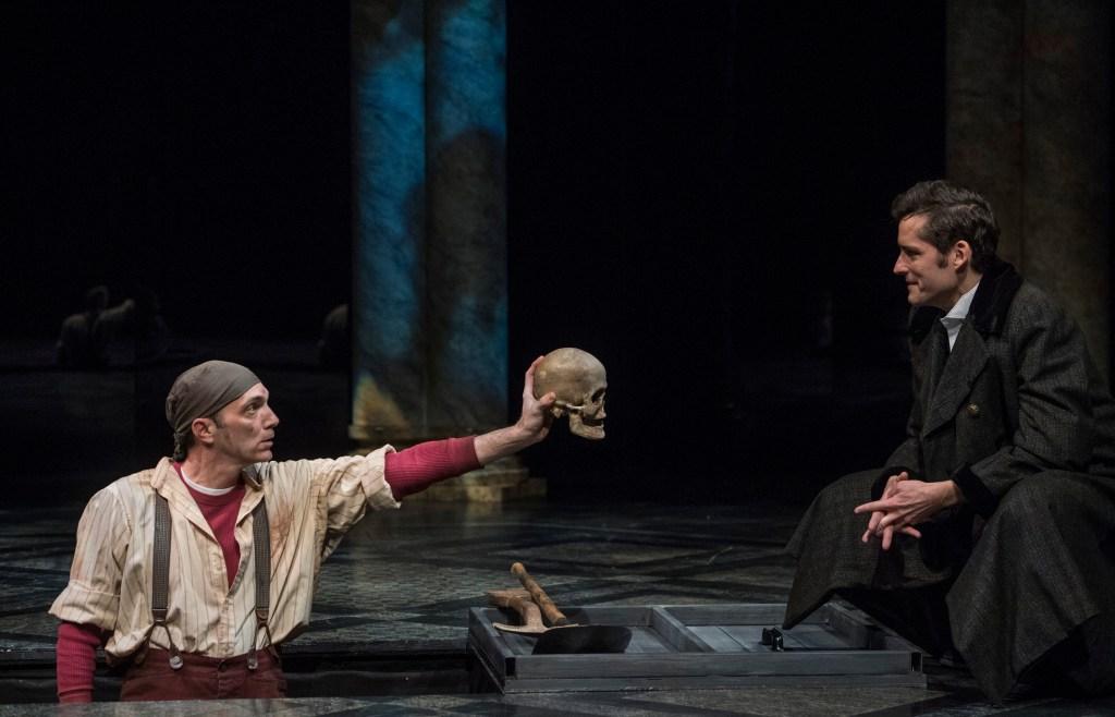 1st Gravedigger (Tony Bingham) shows Hamlet the skull of the deceased court jester Yorick.