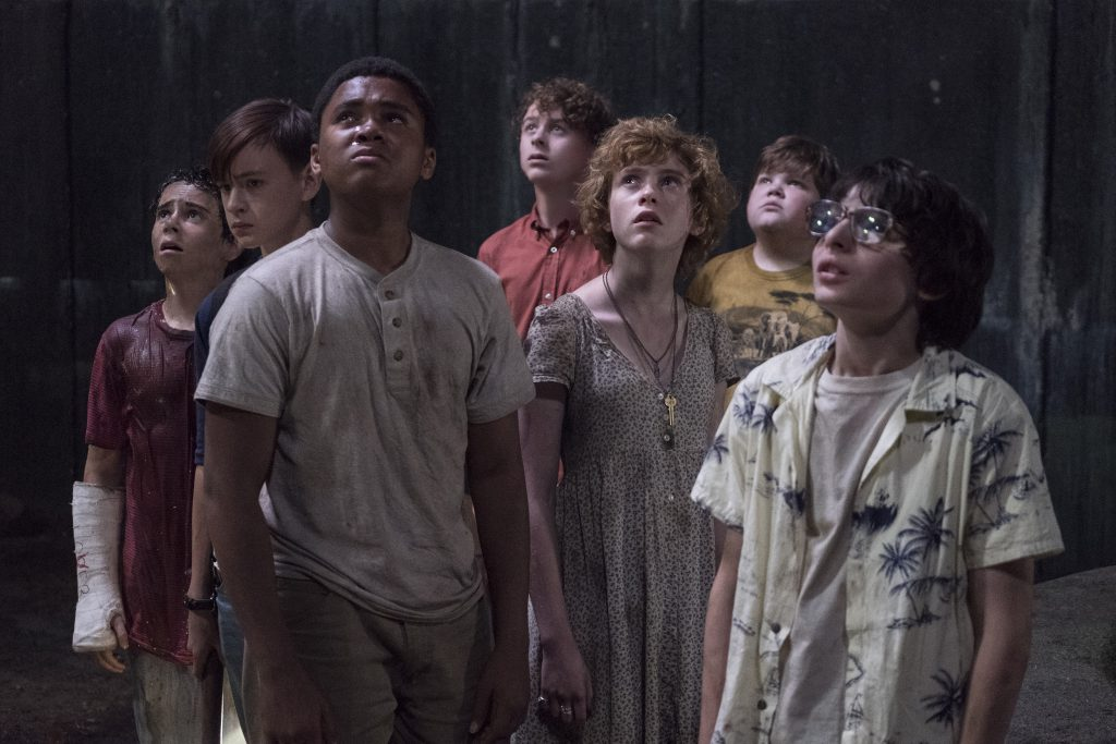 (L-r) Jack Dylan Grazer as Eddie Kaspbrak, Jaeden Lieberher as Bill Denbrough, Chosen Jacobs as Mike Hanlon, Wyatt Oleff as Stanley Uris, Sophia Lillis as Beverly Marsh, Jeremy Ray Taylor as Ben Hanscom and Finn Wolfhard as Richie Tozier look up in horror.